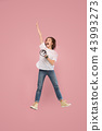 Beautiful young woman jumping with megaphone isolated over pink background 43993273