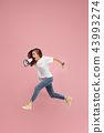 Beautiful young woman jumping with megaphone isolated over pink background 43993274