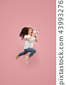 Beautiful young woman jumping with megaphone isolated over pink background 43993276