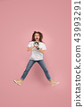 Beautiful young woman jumping with megaphone isolated over pink background 43993291