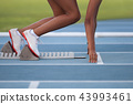 Woman in a starting block on an athletic field 43993461