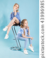 Girls twins in light blue clothes are posing near a bar stool on a blue background. 43996985