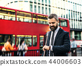 Hipster businessman waiting for the bus in London, checking the time. 44006603