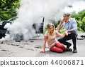 Young woman by the car after an accident and a man making a phone call. 44006871