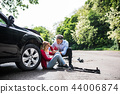 Young woman by the car after an accident and a man helping her. 44006874