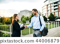 Young businessman and businesswoman shaking hands outdoors. 44006879