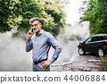 Mature man making a phone call after a car accident, smoke in the background. 44006884