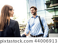 A young businessman and businesswoman shaking hands. 44006913