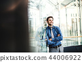 A portrait of a young businessman standing inside a building, arms crossed. 44006922