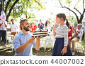 Father giving a cake to a small daughter on a family celebration or a birthday party. 44007002