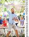 Man jumping with a cake on a family celebration or a garden party outside. 44007003