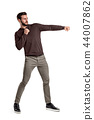 An isolated bearded man in casual clothes punches empty air on a white background. 44007862