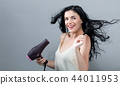 Beautiful young woman holding a hairdryer 44011953