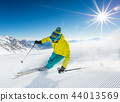 Skier skiing downhill in high mountains 44013569