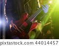 A rocker is playing guitar on stage. 44014457