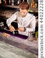 Barman adding cocktail ingredients 44022228