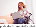 Happy disabled female freelancer working at home 44027044