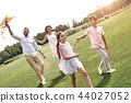 Weekend activities. Family with a kite walking on field in natur 44027052