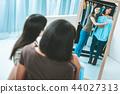 Happy brunettes wearing blue blouse 44027313