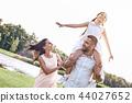 Bonding, Family of three walking on grassy field girl sitting on 44027652