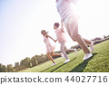 Family walk. Family of three running on grassy field smiling hap 44027716