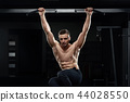 Muscular male athlete pulling up on horizontal bar in dark gym. 44028550