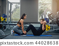 Man doing abdominal crunches press exercise with female personal trainer. 44028638