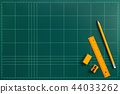Orange stationery on top the green cutting mat 44033262