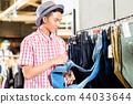 Man choosing jeans in shop 44033644