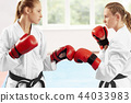 Two female fighter standing in position ready to start fight against big window. 44033983
