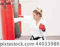 Two strong women boxing red heavy bag in gym. 44033986