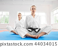 Two young karate girl sittting in lotus position after training in light gym. 44034015