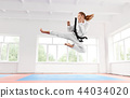 Woman in white kimono with black belt jumping and performing kick. 44034020