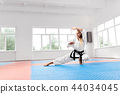 Strong girl wearing in white kimono with black belt practicing karate. 44034045