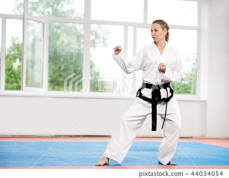 Sporty karate and taekwondo woman in white kimono with black belt. 44034054