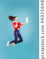 Image of young woman over pink background using laptop computer or tablet gadget while jumping. 44035648