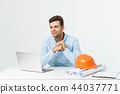 Portrait of young male interior designer or engineer smiling while sitting on his office table. 44037771
