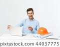 Portrait of young male interior designer or engineer smiling while sitting on his office table. 44037775