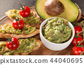 A delicious bowl of Guacamole with fresh ingredients on stone table. 44040695