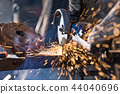 Worker cutting metal with grinder. 44040696