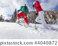 Snowshoe walkers running in powder snow with beautiful sunrise light. 44040872