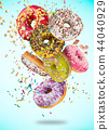 Tasty doughnuts in motion falling on pastel blue background. 44040929