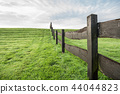 Grass field with wooden fence 44044823