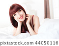 Young woman lying on bed 44050116