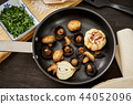 fried mushrooms on a hot pan on an old wooden table 44052096