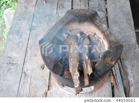 Fireplace for cooking is burning firewood. 44058081