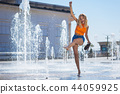 Nice happy young woman playing with water 44059925