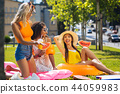 Nice happy young women resting together outdoors 44059983