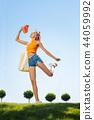 Joyful nice woman jumping on the grass 44059992