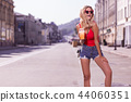 Positive delighted woman standing in the middle of the street 44060351